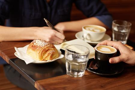 pasteles: Recortar foto de dos personas que se sientan uno frente al otro en una cafetería Foto de archivo