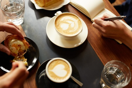 Overhead shot of a hand writing down notes in a notebook next to a cappucino