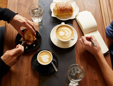 Overhead shot of one person having a croissant and a cappucino taking notes