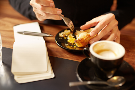 small plate: Cropped shot of a delicious looking half-eaten pastry on a small plate with a mans hands using a fork