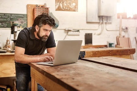 Bearded man who owns a small business, bending over at his work bench to type on his laptop, while working in his workshop and design studio Foto de archivo