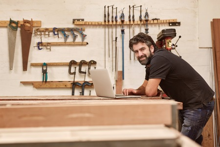 Portrait of a middle-aged artisan in his woodwork workshop with tools on the wall, leaning on his workbench and smiling at the camera while using a laptop