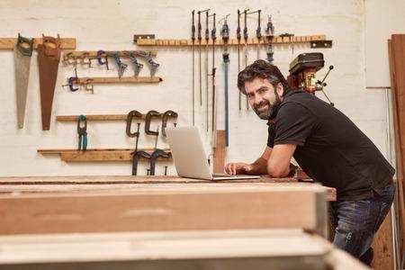 Retrato de un artesano de mediana edad en su taller de carpintería con las herramientas en la pared, apoyado en su mesa de trabajo y sonriendo a la cámara mientras se utiliza un ordenador portátil