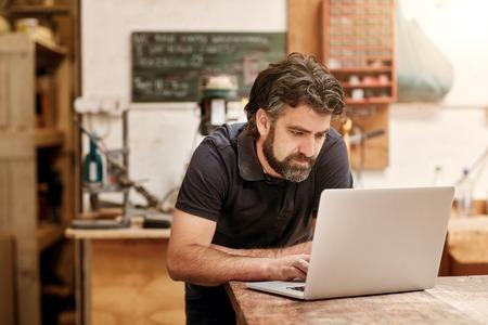 Mannelijke ontwerper en vakman met een ruige baard, die aan zijn laptop op zijn werkbank, in zijn atelier workshop