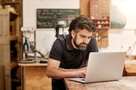 Male designer and craftsman with a rugged beard, working on his laptop at his workbench, in his studio workshop