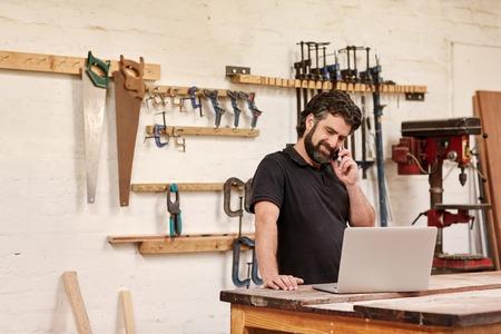 Kleine ondernemer staande in zijn timmerwerkplaats, glimlachen terwijl praten over de telefoon, en te kijken naar zijn laptop, die rust op zijn werkbank, met gereedschap in rijen op de muur achter hem