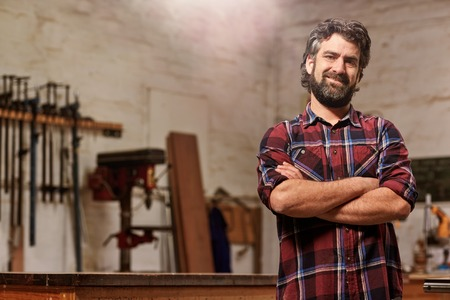 Portrait of a bearded man who owns a small carpentry business, standing in his workshop with with arms folded and showing strong forearms, smiling confidently at the camera Stok Fotoğraf