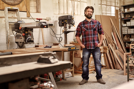Full length portrait of a business owner who runs a carpentry studio, standing confidently with hands in his pockets, smiling at the camera, in his workshop with pieces of wood and woodwork machinery