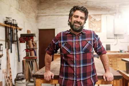Portrait of a smiling craftsman with a rugged beard wearing a checked shirt, standing in his woodwork studio with a wooden workbench and tools on the wall
