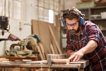 Skilled carpenter cutting a piece of wood in his woodwork workshop, using a circular saw, and wearing safety googles and earmuffs, with other machinery in the background