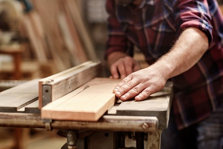 tools: Cropped image of the hands of a skilled craftsman cutting a wooden plank with a circular saw in a workshop