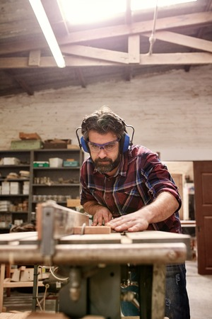 Bearded craftsman carefully cutting through a plank of wood, in his workshop, using a circular saw, and wearing safety goggles and earmuffs