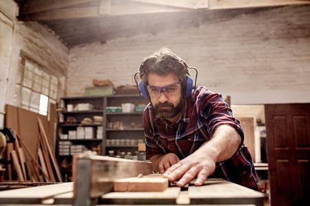 Gelernter Tischler und kleine buiness Eigentümer in seiner Holzwerkstatt arbeiten, mit einer Kreissäge durch ein Holzbrett zu schneiden Standard-Bild - 54601239