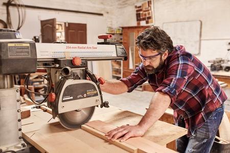 Geschoolde timmerman in zijn workshop houtbewerking, het snijden van een stuk hout met een radiale arm cirkelzaag, en het dragen van een veiligheidsbril