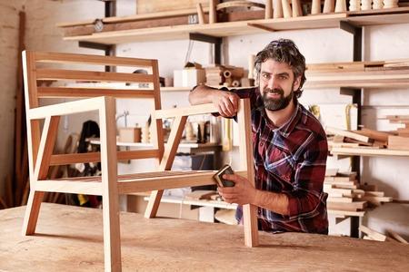 Retrato de un diseñador artesanal, con la nueva pieza de mobiliario, terminando el lijado de la silla en su estudio, con estantes de madera detrás de él Foto de archivo