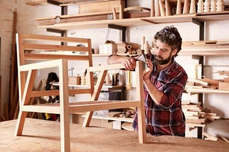 Designer de mobiliário sério lixando cuidadosamente um quadro de cadeira que ele está ocupado fabricando em seu estúdio de madeira, com prateleiras de itens de madeira atrás dele