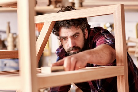 artisan: Portrait of a serious craftsman looking focused and serious as he is sanding down a wooden piece that he has manufactured in his woodkwork studio
