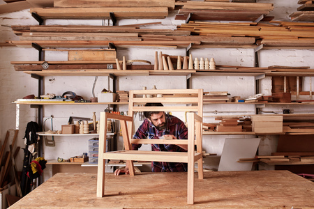 designer chair: Artisan furniture designer and carpenter in his woodwork studio, with shelves of pieces of wood, while working at his workbench, carefully sanding a chair frame
