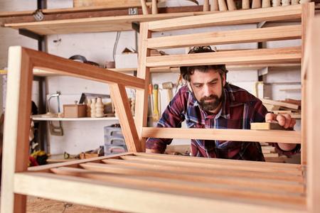 Eigenaar van een onafhankelijke meubels ontwerpen en vervaardigen zaken, het werken op een houten stoel kader dat hij in zijn houtwerk studio heeft gemaakt, zorgvuldig schuren het glad Stockfoto