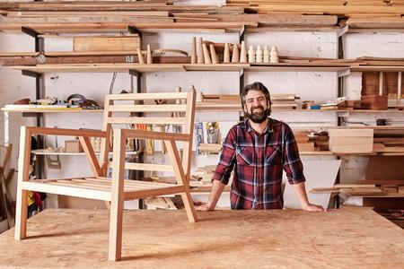 silla de madera: Retrato de un artesano que sonríe con una barba robusto, que descansa sobre su mesa de trabajo con un marco de silla de madera en él, mirando a la cámara, con estantes de tablones de madera y piezas detrás de él