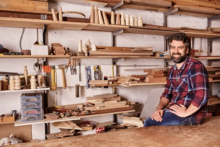 Portrait of a craftsman smiling at the camera while sitting on the edge of his workbench, in his woodwork studio, with long shelves behind him holding planks of wood and hand tools