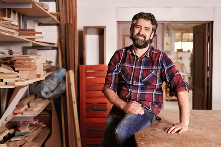 he is different: Smiling craftsman sitting in his woodwork studio for a portrait, with shelves of different  pieces of wood, where he works as a carpenter
