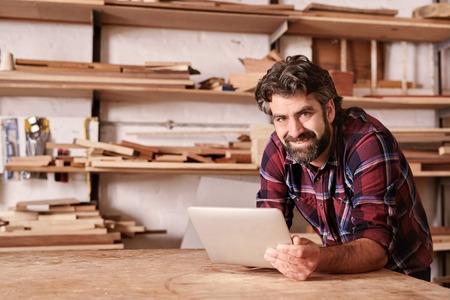 Portret van een kleine bedrijfseigenaar die aan de camera glimlacht, op zijn werkbank rust en een digitale tablet houdt, met houtplanken achter hem in zijn houtwerkstudio