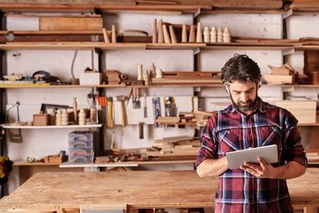 Estudio con carpintería artesanal con estanterías de sujeción de piezas de madera, con un carpintero de pie en su taller utilizando una tableta digital