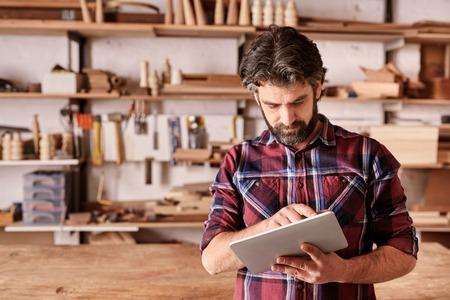 Bebaarde man ontwerper, staande in zijn houtbewerking studio, werkt aan een digitale tablet, met planken van houten stukken achter hem