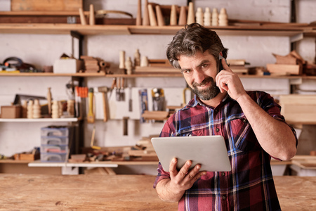 business man phone: Portrait of a carpenter smiling at the camera while listening on his mobile phone, standing in his woodwork studio and holding a digital tablet