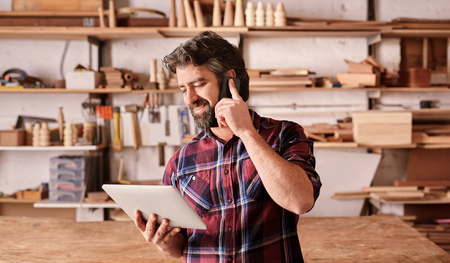 Smiling man with a rugged beard, talking on his mobile phone while looking at a digital tablet in his hand, standing in his woodwork studio Stock Photo