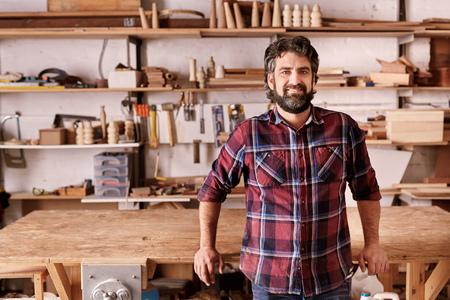 Portret van een zelfstandig ontwerper in zijn meubelproductie workshop, leunend tegen de rand van zijn werkbank, op zoek ontspannen en vol vertrouwen