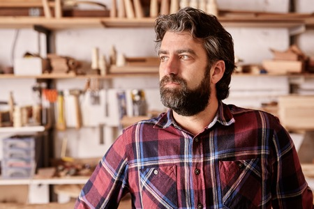 looking away from camera: Portrait of a craftsman and owner of an artisan carpentry business in his workshop, looking away from the camera towards the light with a serious and confident expression. Stock Photo
