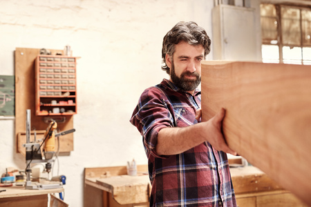 one eye closed: Highly skilled craftsman looking down the length of a wooden plank with one eye closed, checking for straightness and quality, in his workshop Stock Photo