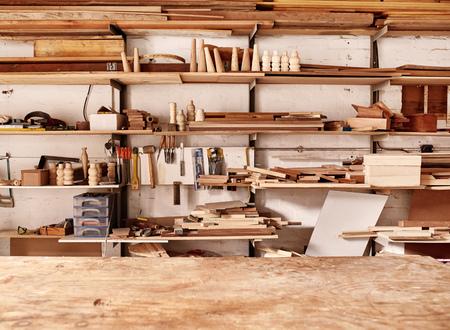 Parede de oficina de carpintaria com muitas prateleiras segurando uma variedade de peças de madeira e tábuas de madeira e algumas ferramentas manuais, com uma bancada de madeira em primeiro plano