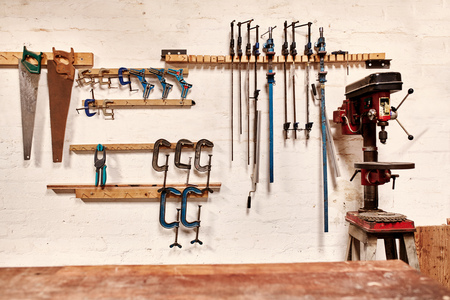 White wall of a woodwork workshop with hand tools hanging in neat rows, a well used drill press on one side and a wooden work bench in the foreground