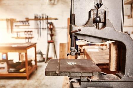 maquinaria: Bien cuidada y bien utilizado plantilla vio máquina en un taller de carpintería de madera, con maquinaria, herramientas y un banco de trabajo en segundo plano