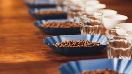 Row of blue containers with fresh roatsed coffee beans alongside coffee cups and water glasses on a wooden table ready for a tasting