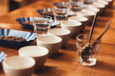 Neat row of cups and containers with fresh roasted coffee beans laid out on a wooden table ready for a tasting, with water glasses and teaspoons