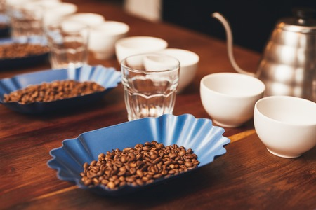 cupping: Containers with coffee beans, cups and water glasses organised in neat rows with a stainless steel kettle, set out in preparation for a coffee tasting Stock Photo