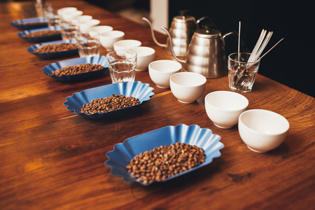 Wooden table top with neat rows of cups, water glasses and blue containers with roated coffee beans laid out in preparation for a professional coffee tasting