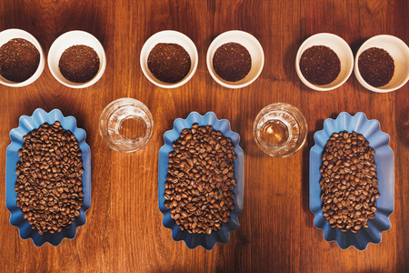 Overhead view of open containers of freshly roasted coffee beans, with water glasses and cups containing ground coffee, set out in perfect rows on a wooden table