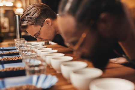 baristas: Professional baristas leaning over a row of freshly ground coffee, taking in the aroma, at a coffee tasting with different varieties of roasted coffee beans