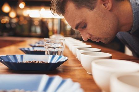 Casucasian Mann über einen hölzernen Theke gelehnt Set mit ordentlichen Reihen von Containern mit einer Vielzahl von Kaffeebohnen, Wassergläser und Kaffeetassen, das frische Aroma von gemahlenem Kaffee riechend