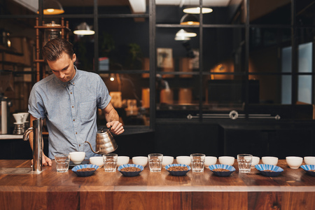 Professional barista in a modern roastery preparing for a coffee tasting session, at a wooden counter laid out with neat rows of cups, water glasses and open containers of coffee beans