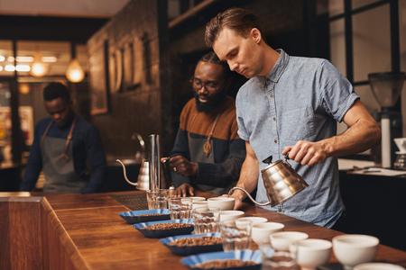 grano de cafe: Tres baristas en el trabajo en una planta tostadora moderna preparando para una degustación de café, con hileras de copas, vasos de agua y contenedores abiertos de una variedad de granos tostados