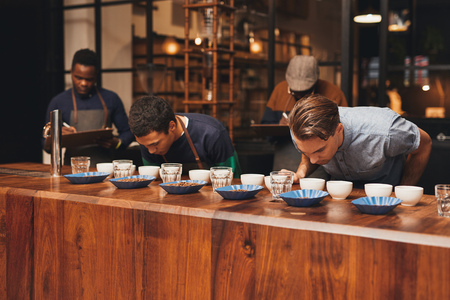 baristas: Two baristas doing coffee training in a modern roastery with two managers taking notes, while baristas are leaning over the wooden counter with rows of a variety of coffee beans Stock Photo