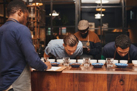 baristas: Professional baristas training new employees at a modern roastery, with rows of different coffee varieties on a wooden counter