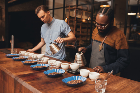 baristas: African and caucasian baristas at a wooden counter in a modern roastery, with rows of coffee cups and roasted beans preparing for a tasting
