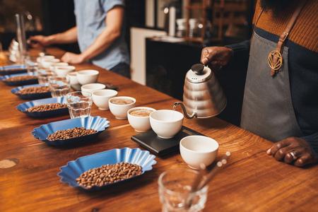 Bijgesneden shot van een volk op een houten tafel met keurige rijen van open containers van gebrande koffiebonen ingesteld, opleiding tot professionele barista's worden tijdens het gieten van water in kopjes gemalen koffie